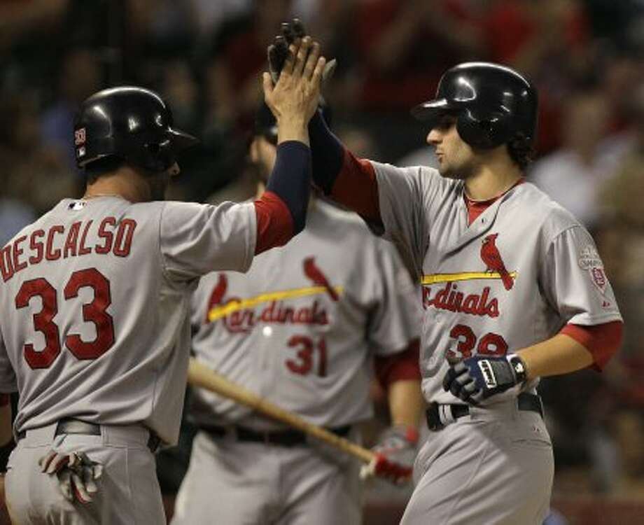St. Louis Cardinals' Daniel Descalso and Pete Kozma celebrate a two-run home run hit by Kozma during the second inning. (Melissa Phillip / © 2012 Houston Chronicle)