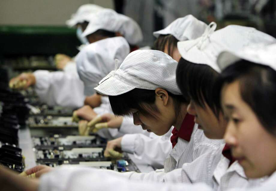 Employees work on the production line at the Foxconn Technology Group complex in Shenzhen, China. Foxconn has faced significant criticism over working conditions at the Chinese facilities where Apple products are assembled. Photo: Kin Cheung, STF / AP