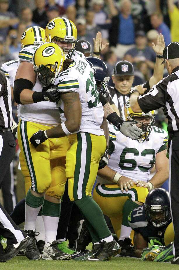 Green Bay Packers T.J. Lang, left, congratulates teammate Cedric Benson, second from left, after Benson scores a touchdown against the Seattle Seahawks in the second half of an NFL football game, Monday, Sept. 24, 2012, in Seattle. Photo: AP
