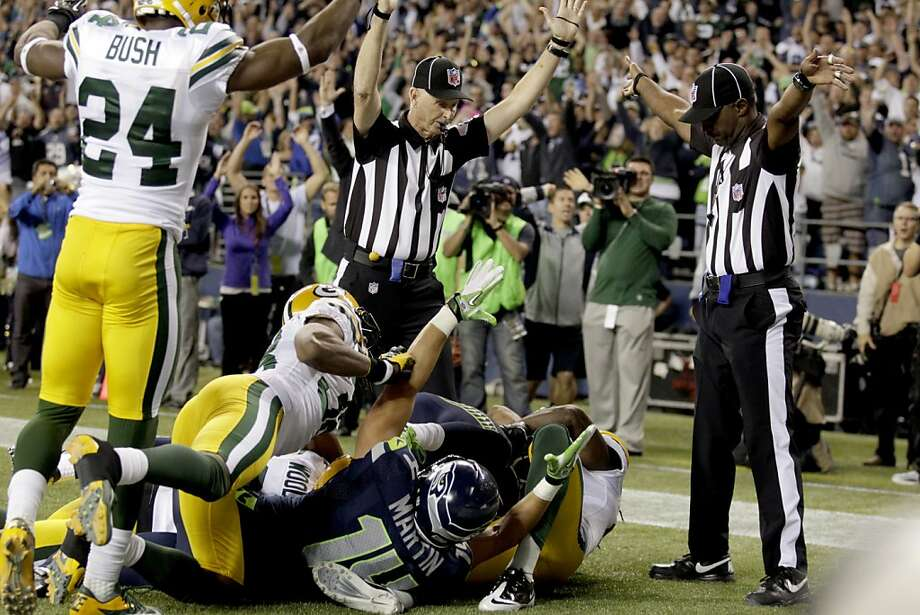 Officials signal a touchdown by Seattle Seahawks wide receiver Golden Tate, obscured, on the last play of an NFL football game against the Green Bay Packers, Monday, Sept. 24, 2012, in Seattle. The Seahawks won 14-12. (AP Photo/Stephen Brashear) Photo: Stephen Brashear, Associated Press