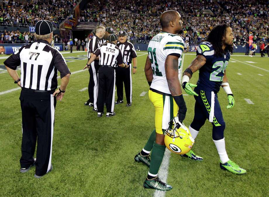 Officials discuss the final play of the game as Green Bay Packers' Charles Woodson, second from right, and Seattle Seahawks' Earl Thomas, right, leave the field in the second half of an NFL football game, Monday, Sept. 24, 2012, in Seattle. The final play was ruled a Seattle touchdown as the Seahawks defeated the Packers 14-12. Photo: AP