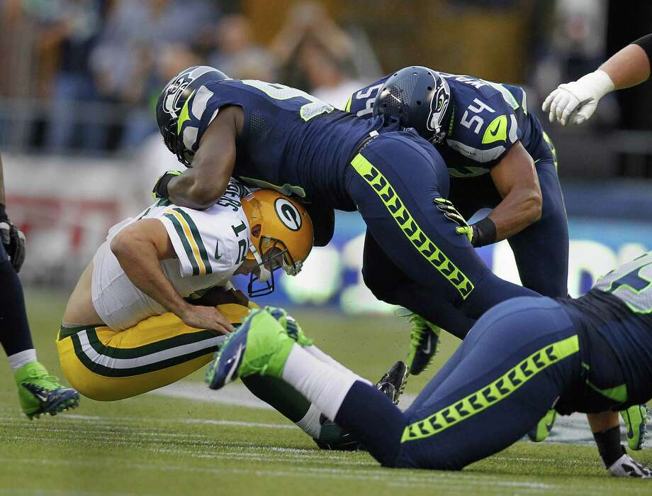 Seattle's Chris Clemons takes Green Bay quarterback Aaron Rodgers to the ground for one of his four sacks Monday night. Rodgers was sacked eight times. Photo: Rick Wood / Milwaukee Journal Sentinel