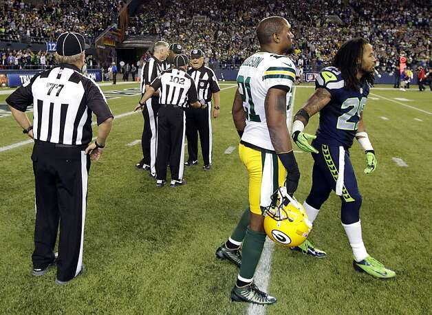 Officials discuss the final play of the game as Green Bay Packers' Charles Woodson, second from right, and Seattle Seahawks' Earl Thomas, right, leave the field in the second half of an NFL football game, Monday, Sept. 24, 2012, in Seattle. The final play was ruled a Seattle touchdown as the Seahawks defeated the Packers 14-12. (AP Photo/Ted S. Warren) Photo: Ted S. Warren, Associated Press