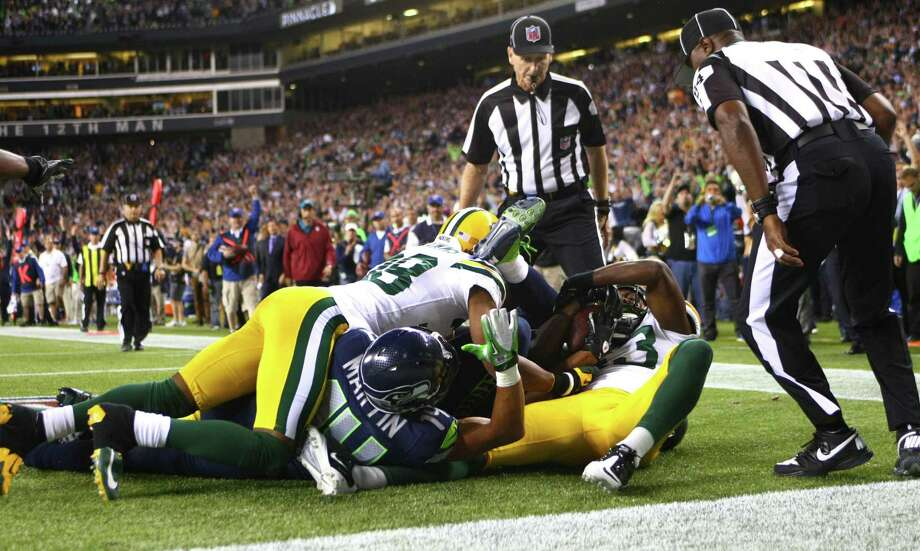 Referee Wayne Elliott, center, and back judge Derrick Rhone-Dunn look on as Seattle Seahawks player Golden Tate and Green Bay Packers player M.D. Jennings fight for the ball in a play that resulted in  a Seattle Seahawks touchdown in the final second of the Seattle Seahawks and Green Bay Packers game. The controversial call put the Seahawks over the Packers to win 14 to 12. Photo: JOSHUA TRUJILLO / SEATTLEPI.COM