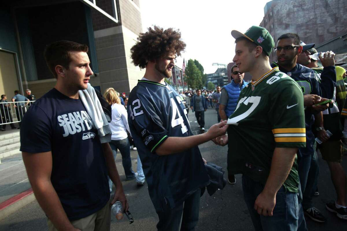 Seattle Seahawks fan Andrew Rucker, center, ribs Josh Macri over his Green Bay Packers jersey outside the stadium during Monday Night Football on September 24, 2012 at CenturyLink FIeld in Seattle.