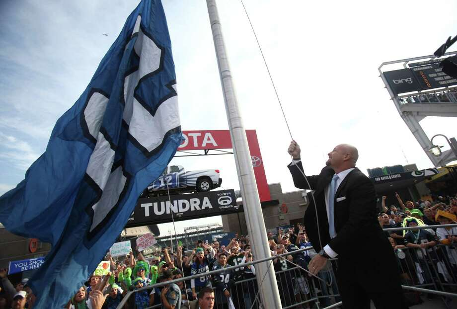 Former Seattle Seahawks quarterback Trent Dilfer raises the 12th Man Flag. Photo: JOSHUA TRUJILLO / SEATTLEPI.COM