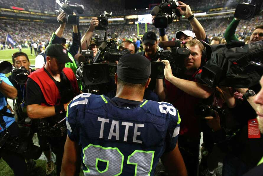 Seattle Seahawks player Golden Tate is surrounded by cameras after his game winning, and controversi
