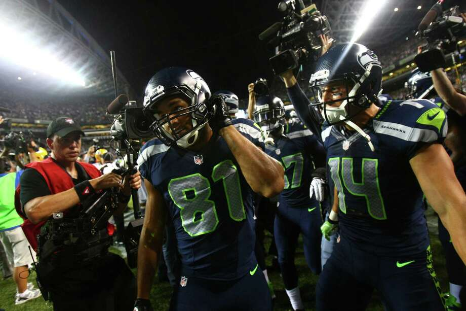 Seattle Seahawks player Golden Tate emerges from a mob of players and cameras after his game winning, and controversial touchdown. Photo: JOSHUA TRUJILLO / SEATTLEPI.COM