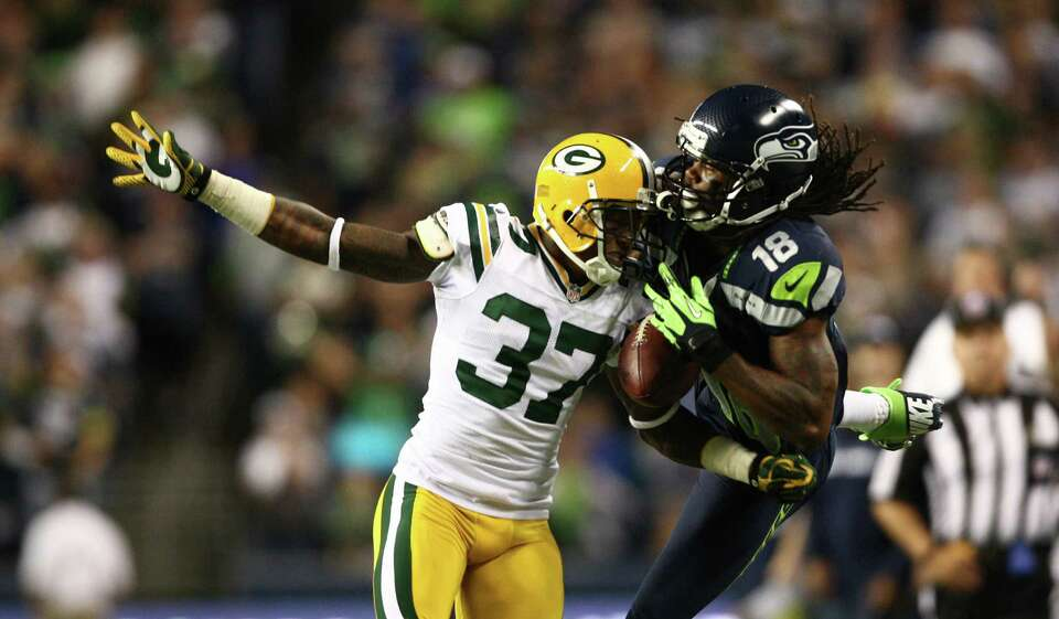 Seattle Seahawks player Sidney Rice (18) has a pass broken up by Green Bay Packers player Sam Shield