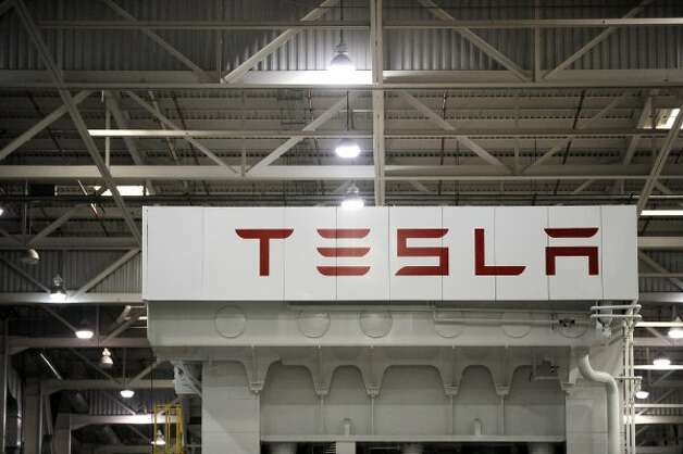 A Tesla sign decorates inside the factory in Fremont, Calif., Wednesday, June 13, 2012. On June 22, Tesla Motors will begin delivering its all-electric Model S luxury sedan. It is only the second car ever produced by Tesla, and first to be built at Tesla's own factory. (Erik Verduzco / Special to The Chronicle)