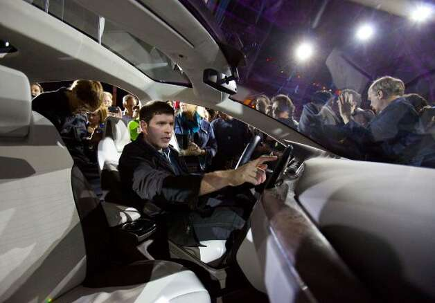 An attendee checks out Tesla Motors Inc.'s Model X vehicle at its unveiling at Tesla's design studio in Hawthorne, California, U.S., on Thursday, Feb. 9, 2012. The Model X, touted by Tesla as faster than Porsche AG's 911 sports car and roomier than Audi AG's Q7 SUV, will be built in 2013 at the company's Fremont, California, plant that starts making the Model S this year. Photographer: Tim Rue/Bloomberg (Tim Rue / Bloomberg)