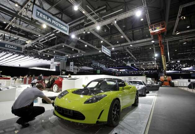 A man works to prepare a Tesla automobile on the company's stand, ahead of the opening press day at the Geneva International Motor Show in Geneva, Switzerland, on Monday, March 5, 2012. The 82nd Geneva International Motor Show will showcase the latest models from the auto industry's leading manufacturers at the Palexpo exhibition centre this week. Photographer: Jason Alden/Bloomberg (Jason Alden / Bloomberg)