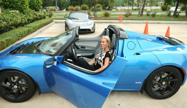 Erin Link, of The Woodlands, tries on the driver's seat of a Tag Heuer Tesla Roadster at a test drive event at Donoho's in The Woodlands on Thursday. The electric super car accelerates from 0-60 mph in 3.7 seconds and uses no gasoline and produces no fumes. The car is powered by a battery that powers the car 250 miles on a single charge and can be plugged into any conventional outlet. Photo by Jerry Baker (Jerry Baker / For the Chronicle)