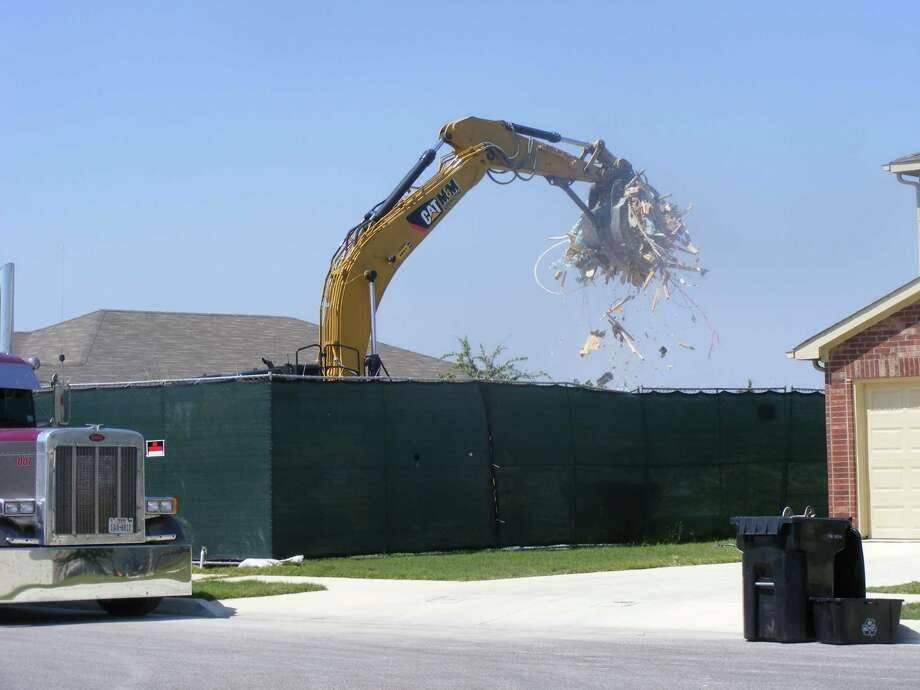 Pulte Homes work crews demolish a home in the Fairhaven subdivision of Schertz. Photo: David DeKunder / NE Herald