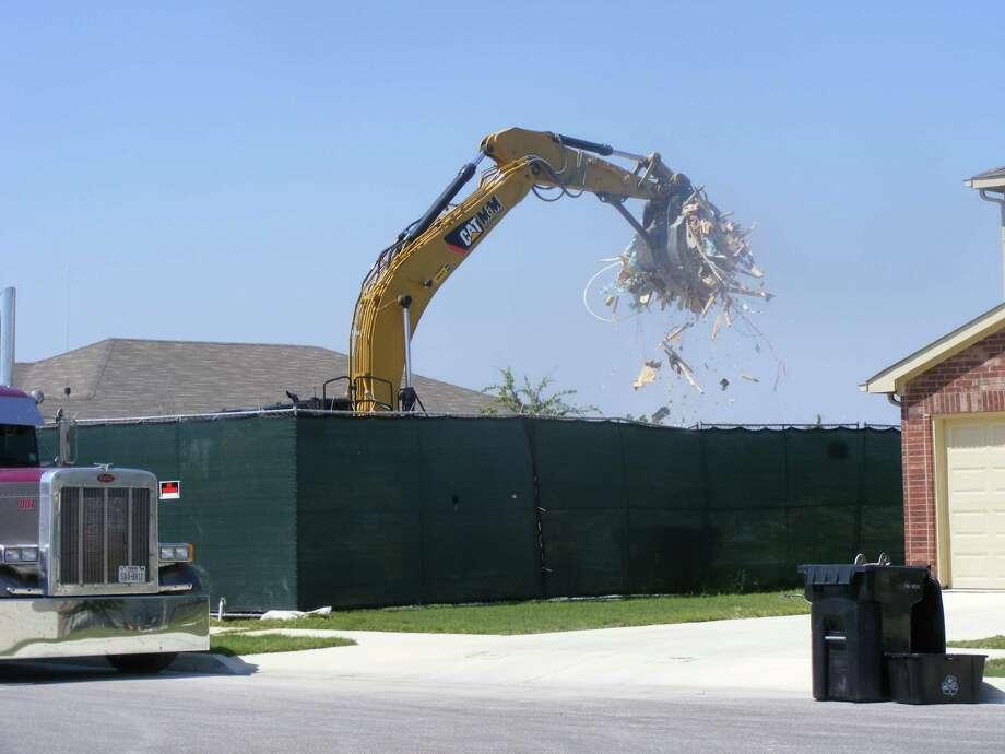 Pulte Homes work crews demolish a home in the Fairhaven subdivision of Schertz. Photo: David DeKunder / NE Herald