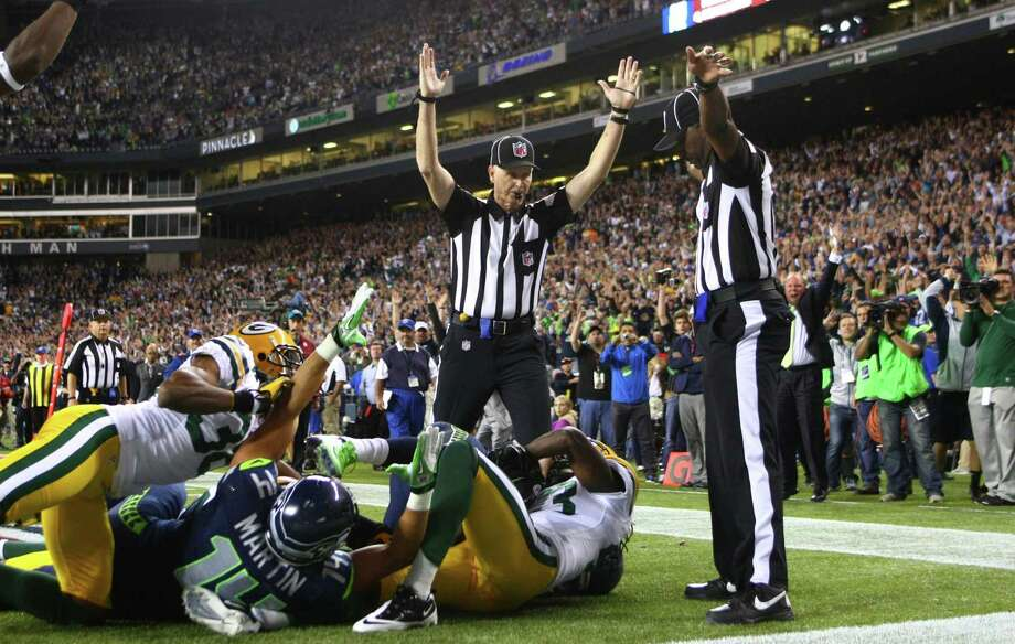 Side Judge Lane Easley, center, looks at back judge Derrick  Rhone-Dunn as Elliott calls a Seattle Seahawks touchdown catch by Golden  Tate in the final second of the Seattle Seahawks and Green Bay Packers  game Monday Night Football game on September 24, 2012 at CenturyLink  FIeld in Seattle. The controversial call put the Seahawks over the  Packers to win 14 to 12. Photo: JOSHUA TRUJILLO / SEATTLEPI.COM