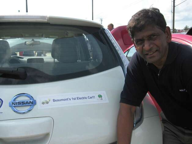 "G.N. Reddy, associate professor of electrical engineering at Lamar University, shows off his bumper sticker on his 2011 Nissan Leaf all-electric car -- ""Beaumont's 1st Electric Car."" Reddy took part in the opening of a new electric-car charging station at Lamar's Montagne Center. There is another station at Lamar Institute of Technology, installed by Entergy Corp. to gauge how much usage there might be among Lamar students, faculty and staff. Dan Wallach/The Enterprise Photo: Dan Wallach"