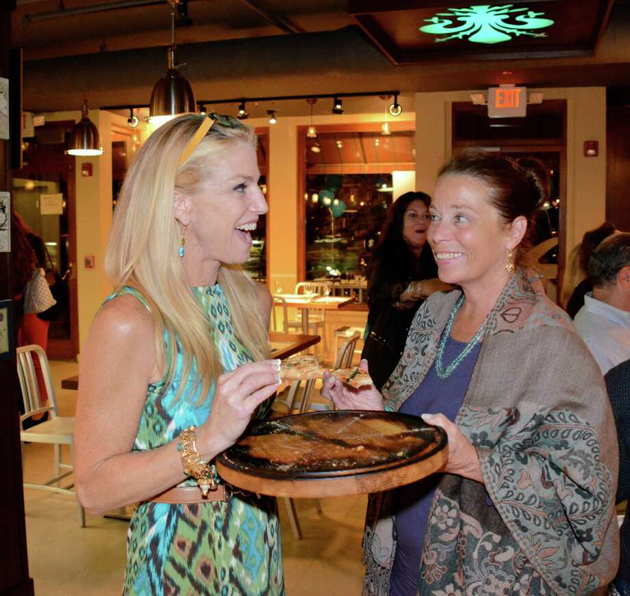 Devon Fleming and Kathryn Blankenship enjoy a few slices of pizza at the opening of the Tuscan Pizza Bar last Thursday night, September 20, 2012, in New Canaan, Conn. Photo: Jeanna Petersen Shepard