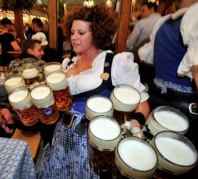 A waitress carries beer mugss in the Hofbraeuhaus beer tent at the Theresienwiese Oktoberfest fair grounds in Munich, Germany, on Monday,  (BY FRANK LEONHARDT/ARDT/AFP/GettyImages) Photo: Ap/getty
