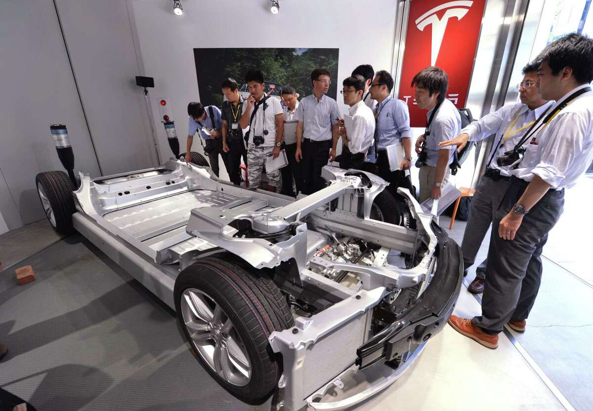 Japanese reporters satnd next to a chassis of US electric vehicle maker Tesla Motors' premium electric Model S sedan during a press preview in Tokyo on August 30, 2012. Model S is the first premium sedan designed from the ground up to take full advantage of electric vehicle architecture. AFP PHOTO / KAZUHIRO NOGIKAZUHIRO NOGI/AFP/GettyImages (AFP/Getty Images)