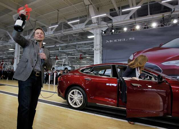 In this file photo, Tesla Motors Inc. CEO Elon Musk holds up a bottle of wine given as a gift from one of their first customers, right, during a rally at the Tesla factory in Fremont. Photo: Paul Sakuma, Associated Press / AP
