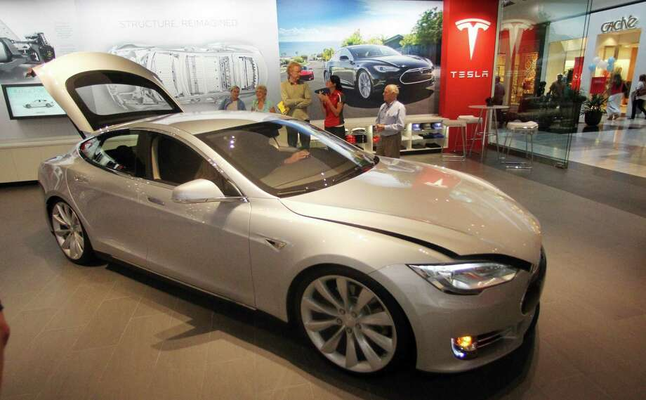 A Tesla Model S is shown in the showroom at the Washington Square Mall, Friday, July 20, 2012, in Portland, Ore. Tesla Motors only has 24 stores in the world, and now one of them is at Washington Square Mall in Portland. The company produces electric cars and hopes their product will be a hit with eco-conscious Oregonians. The cars can go from zero to 60 mph in less than six seconds, all without a drop of gasoline. (AP Photo/Rick Bowmer) Photo: Rick Bowmer, Associated Press / AP