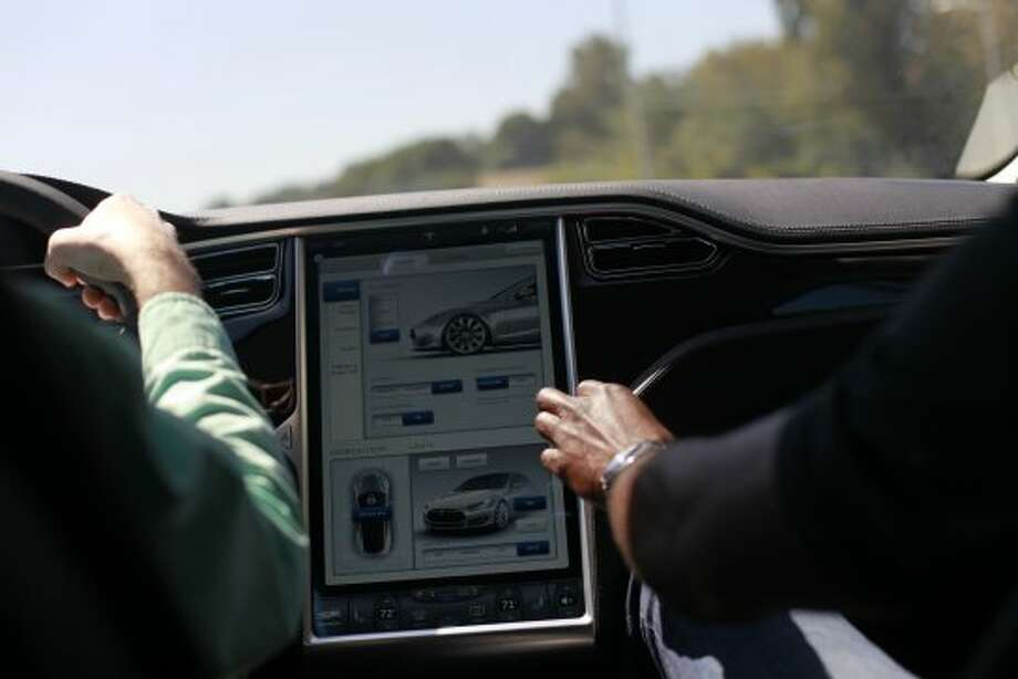 Members of the local press test drive the Tesla Model S sedan at the Tesla Headquarters in Palo Alto, Calif.