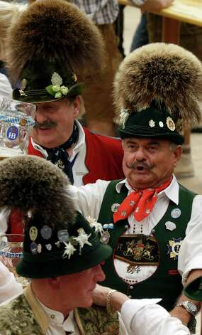 Silly hats flourish at Oktoberfest. These men were dressed in traditional Bavarian outfits on Tuesday.. (AP Photo/Matthias Schrader) Photo: Ap/getty