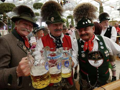 """Traditionally dressed Bavarian men raise their steins and enjoy a sunny day of the famous Bavarian """"Oktoberfest"""" beer festival in Munich, southern Germany, Tuesday, Sept. 25, 2012. The world's largest beer festival, to be held from Sept. 22 to Oct. 7, 2012 will see some million visitors. (AP Photo/Matthias Schrader) Photo: Ap/getty"""