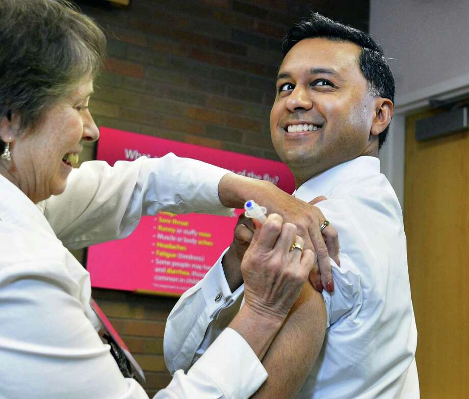 State Health Commissioner Dr. Nirav R. Shah gets his flu shot from state Health Department registered nurse Lynn Pollock, left, at the Wadsworth Center's David Axelrod Institute on Tuesday, Sept. 25, 2012.  (John Carl D'Annibale / Times Union) Photo: John Carl D'Annibale / 00019400A