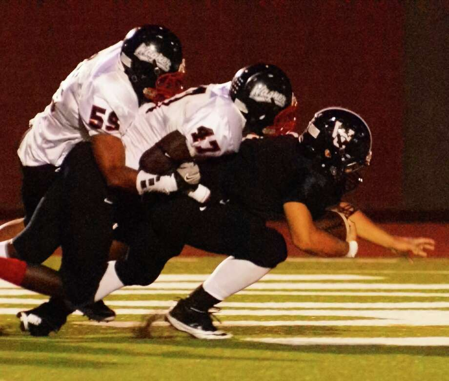Wagner linebacker Adeo Davis (59) and lineman Duron Smith (47) combine to bring down a Churchill ball carrier during the Thunderbirds' thrilling 27-21 come-from-behind victory Friday. Photo: Lavon Brown / For The NE Herald