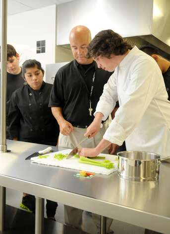 Conroe Independent School District culinary instructor Bill Prisock, center, helps Jared Schaeter with his knife skills during a class as Sean Avila, left, and Brenda Rosendo look on. Photo: Jerry Baker