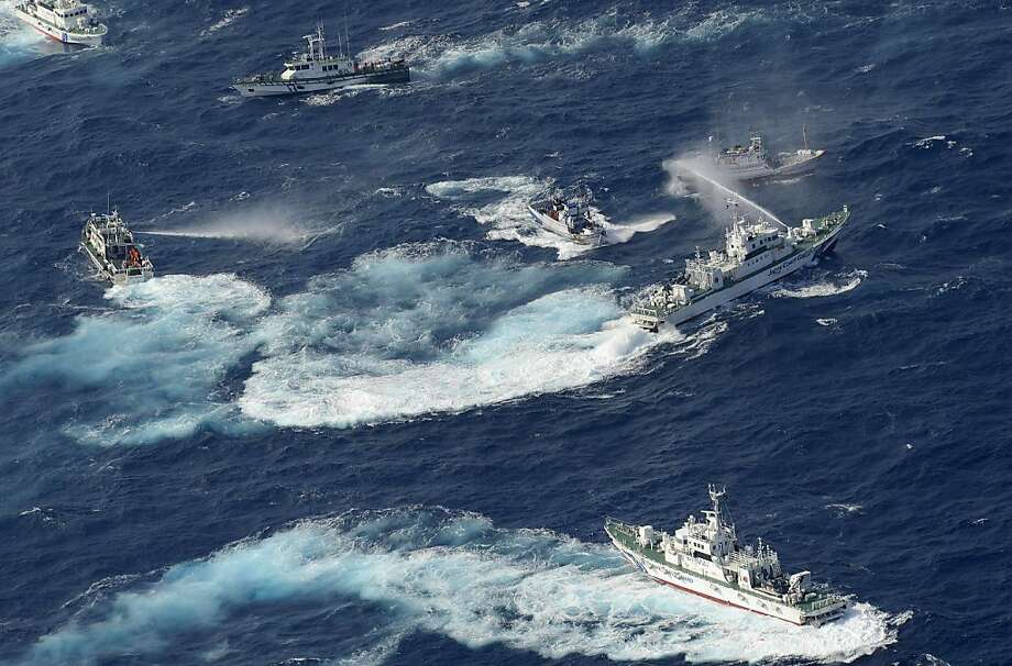 A Japan Coast Guard vessel (R) sprays water against Taiwanese fishing boats, while a Taiwanese coast guard ship (L) also sprays water in the East China Sea near Senkaku islands as known in Japanese or Diaoyu Islands in Chinese on September 25, 2012.  Coastguard vessels from Japan and Taiwan duelled with water cannon after dozens of Taiwanese boats escorted by patrol ships sailed into waters around the Tokyo-controlled islands. Photo: Yomiuri Shimbun, AFP/Getty Images