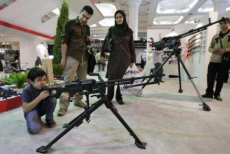 That's my boy: As Mom looks on, 8-year-old Alireza Taromi mows 