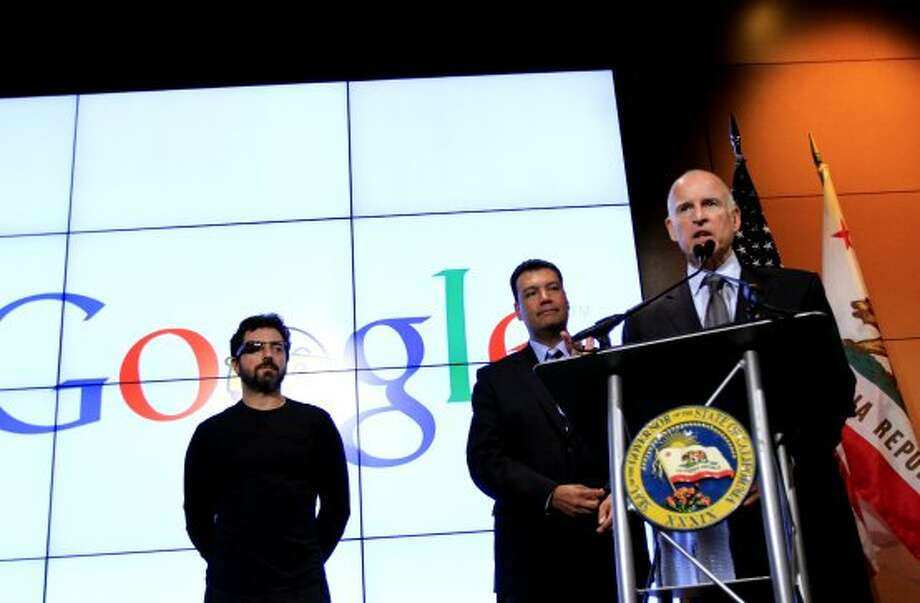 Gov. Jerry Brown speaks at Google headquarters in Mountain View, Calif., Tuesday, September 25, 2012, after signing a new bill regulating the ability of still-experimental driverless vehicles to operate on California roads.  Listening are Google co-founder Sergey Brin, left, and Senator Alex Padilla, center. (Sarah Rice / Special to The Chronicle)