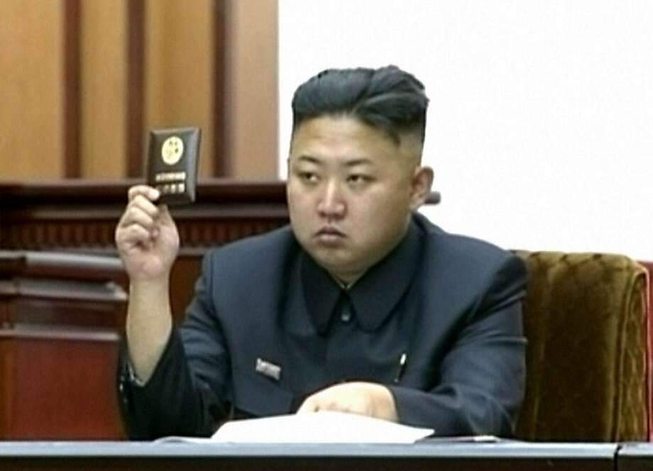 In this video image taken from KRT, North Korean leader Kim Jong Un holds up his credential at the Supreme People's Assembly's second meeting of the year, in Pyongyang, North Korea, Tuesday, Sept. 25, 2012. North Korea's parliament convened Tuesday for the second time in six months, passing a law that adds one year of compulsory education for children in the socialist nation, the first publicly-announced policy change under leader Kim. (AP Photo/KRT via AP video) NORTH KOREA OUT Photo: Associated Press