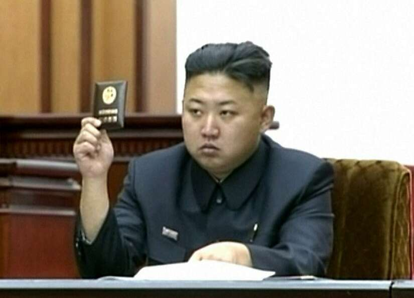 In this video image taken from KRT, North Korean leader Kim Jong Un holds up his credential at the S