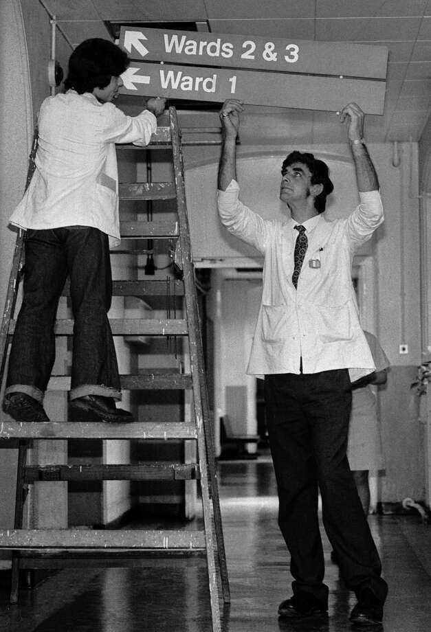 OK, the man who originally occupied Chewbacca's suit was English actor Peter Mayhew (right), who is 7 feet, 3 inches tall. That helped with his other job, as an orderly at King's College Hospital, in London. Here, he helps put up signs to the wards on June 3, 1977. Photo: Colin Davey, Getty Images / 2007 Getty Images