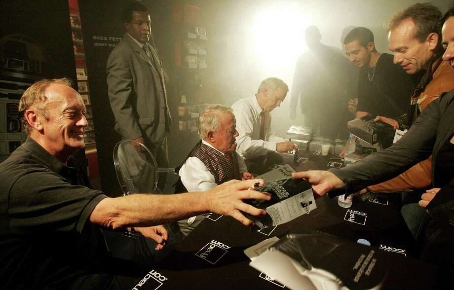Here, Kenny Baker signs autographs between actors Kenneth Colley, left, who played Imperial Navy Admiral Firmus Piett and Jeremy Bulloch, who portrayed bounty hunter Boba Fett on September 21, 2004 in Paris. Photo: THOMAS COEX, AFP/Getty Images / 2004 AFP