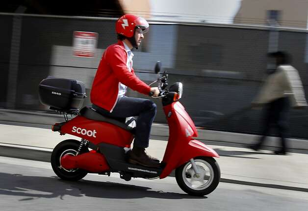 Scoot founder Michael Keating drives a scooter down a San Francisco alley. The service is launching with 60 scooters available at four stations in SoMa. Photo: Brant Ward, The Chronicle