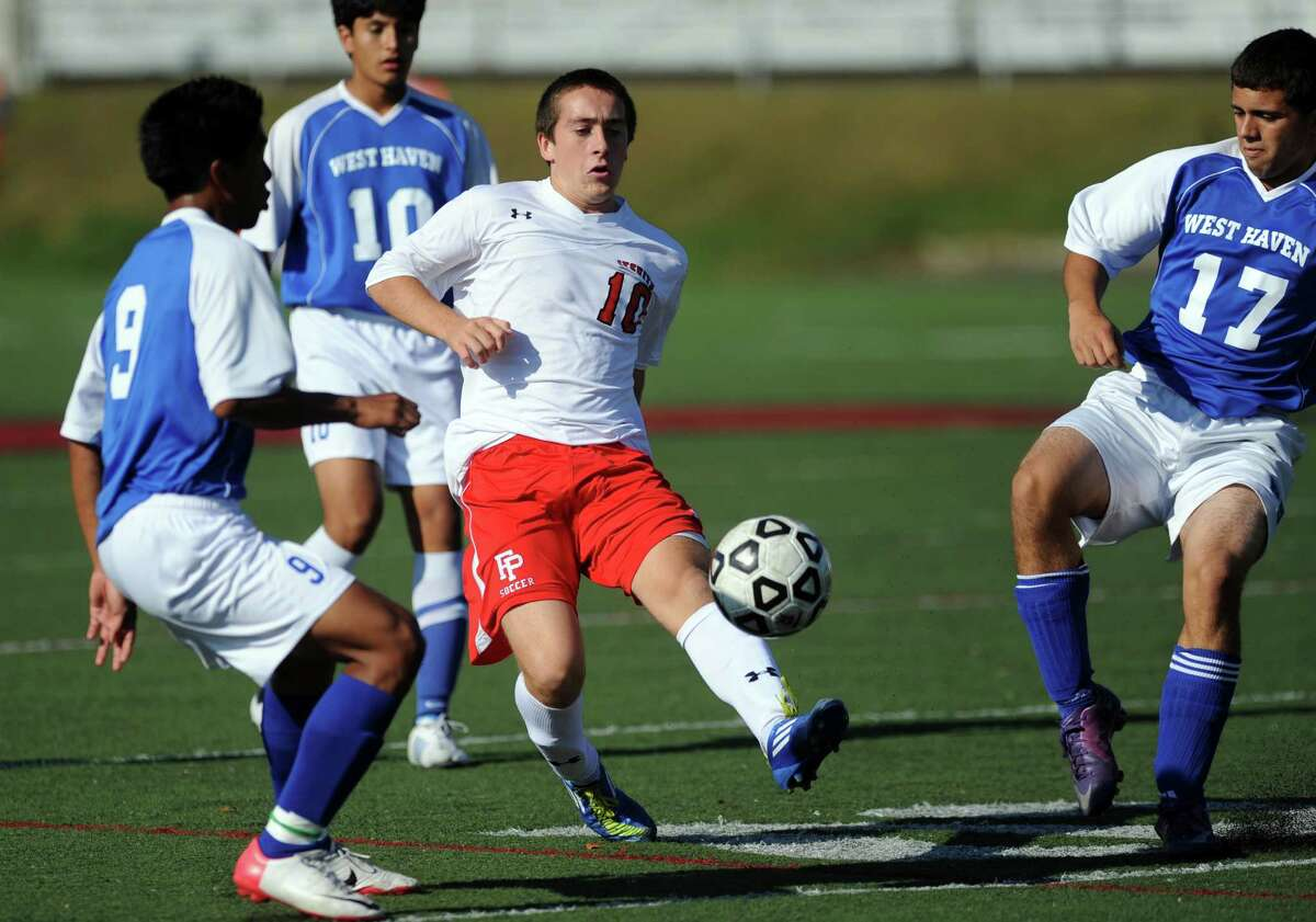 Fairfield Prep's Davie Bruton controls the ball as West Haven's Alexis Garcia, left, and Frederico Dasilva defend during their soccer match Tuesday, Sept. 25, 2012 at Fairfield Prep.
