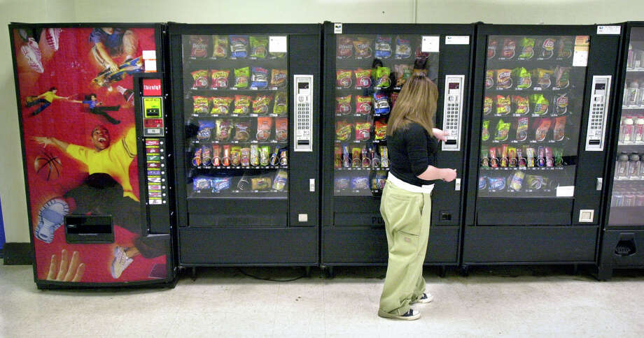 A student purchases a brown sugar Pop-Tart from a vending machine  outside a school cafeteria in Wichita, Kan. Children don't always understand how packaging information lists calorie content for snacks. Photo: File Photo, Associated Press / The Wichita Eagle