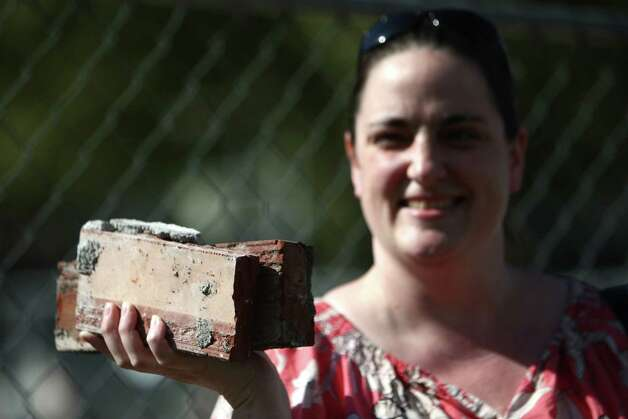 Shannon Presley holds some bricks as workers continue to tear down the former Skoochies dance club on Tuesday, September 25, 2012 near Seattle Center. The building holds memories for many young people that grew up in the 90s. Photo: JOSHUA TRUJILLO / SEATTLEPI.COM