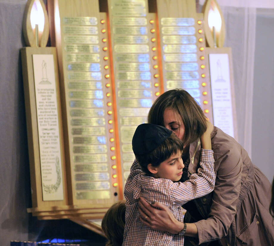 Daisy Florin of Greenwich gives a hug to her son, Sam, 9, after they lit candles in memory of loved ones during the Chabad Lubavitch of Greenwich Yom Kippur service at Carmel Academy in Greenwich, Tuesday, Sept. 25, 2012. Yom Kippur, also known as the Day of Atonement and the holiest day of the year for the Jewish people, began on the evening of Sept. 25 and ends on the evening of Sept. 26. Photo: Bob Luckey / Greenwich Time