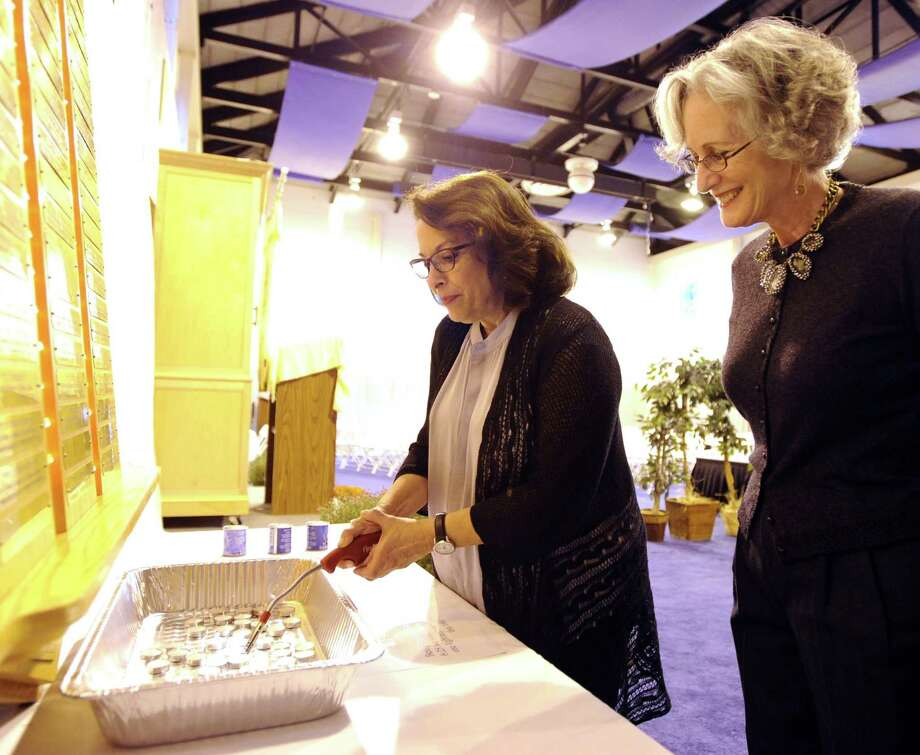 Chabad Lubavitch of Greenwich member Paula Greenstein, left, lights a candle as fellow member Sandy Oster looks on during the Yom Kippur service at Carmel Academy in Greenwich, Tuesday, Sept. 25, 2012. Yom Kippur, also known as the Day of Atonement and the holiest day of the year for the Jewish people, began on the evening of Sept. 25 and ends on the evening of Sept. 26. Photo: Bob Luckey / Greenwich Time