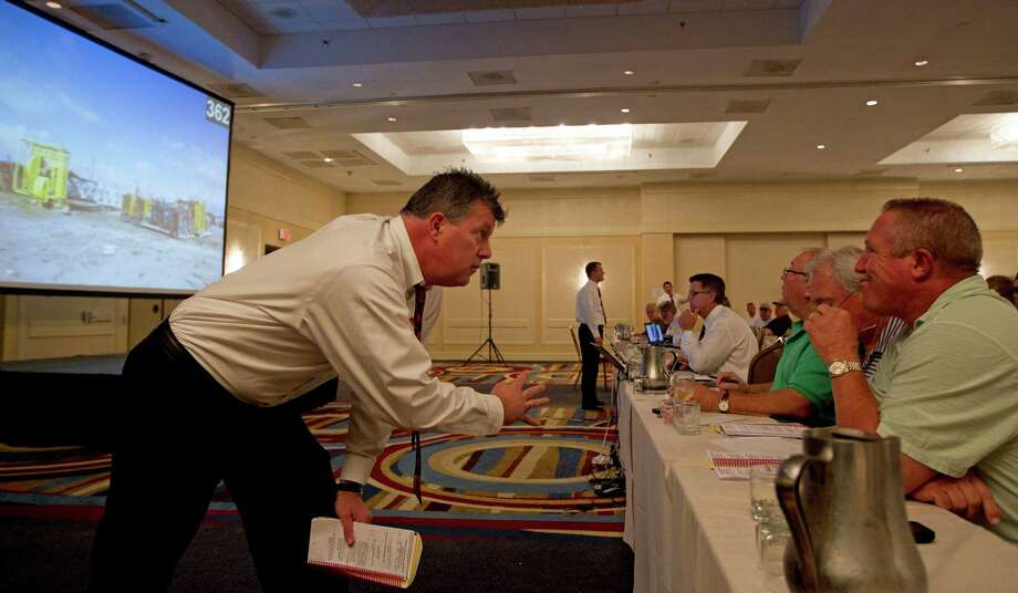 Kenny Garman, left, with auction organizer Kruse Energy and Equipment, checks a bid with Bridges Equipment LTD's Jimmy Bridges during an auction Tuesday at the the Sheraton North Houston at George Bush Intercontinental Airport. Photo: James Nielsen / © Houston Chronicle 2012