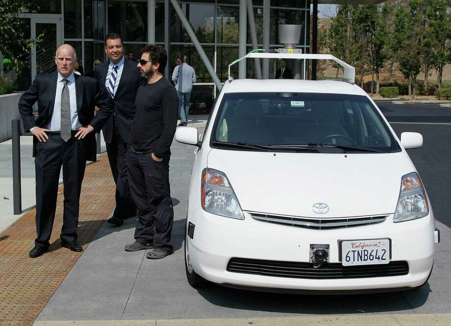 From left, California Gov. Edmund G Brown Jr., state Senator Alex Padilla and Google co-founder Sergey Brin stand by a driverless car they arrived in at Google headquarters in Mountain View, Calif., Tuesday, Sept. 25, 2012.  Brown visited Google to sign legislation for driverless cars. The legislation will open the way for driverless cars in the state. Google, which has been developing autonomous car technology and lobbying for the legislation has a fleet of driverless cars that has logged more than 300,000 miles (482,780 kilometers) of self-driving on California roads. (AP Photo/Eric Risberg) Photo: Eric Risberg