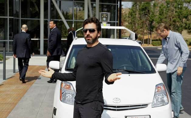 Google co-founder Sergey Brin gestures after riding in a driverless car with California Gov. Edmund G Brown Jr., left, and state Senator Alex Padilla, second from left, to a bill signing for driverless cars at Google headquarters in Mountain View, Calif., Tuesday, Sept. 25, 2012.  The legislation will open the way for driverless cars in the state. Google, which has been developing autonomous car technology and lobbying for the legislation has a fleet of driverless cars that has logged more than 300,000 miles (482,780 kilometers) of self-driving on California roads. (AP Photo/Eric Risberg) Photo: Eric Risberg