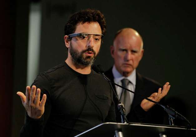 Google co-founder Sergey Brin, left, wearing internet glasses, gestures while speaking as California Gov. Edmund G. Brown Jr., right, listens during a bill signing for driverless cars at Google headquarters in Mountain View, Calif., Tuesday, Sept. 25, 2012.  The legislation will open the way for driverless cars in the state. Google, which has been developing autonomous car technology and lobbying for the legislation has a fleet of driverless cars that has logged more than 300,000 miles (482,780 kilometers) of self-driving on California roads. (AP Photo/Eric Risberg) Photo: Eric Risberg