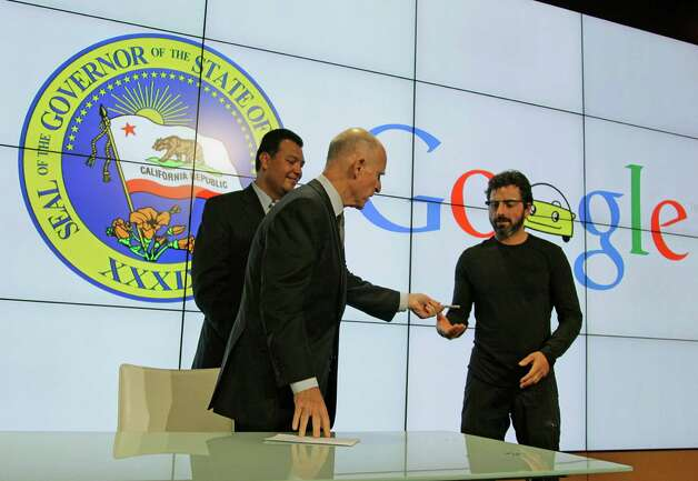 California Gov. Edmund G Brown Jr., center, hands his pen to Google co-founder Sergey Brin, right, after a bill signing for driverless cars at Google headquarters as state Senator Alex Padilla, left, looks on in Mountain View, Calif., Tuesday, Sept. 25, 2012.  The legislation will open the way for driverless cars in the state. Google, which has been developing autonomous car technology and lobbying for the legislation has a fleet of driverless cars that has logged more than 300,000 miles (482,780 kilometers) of self-driving on California roads. (AP Photo/Eric Risberg) Photo: Eric Risberg